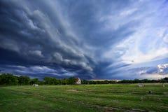猛冲飞行在与绿草的领域的黑暗的云彩 免版税图库摄影