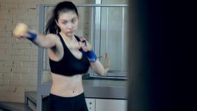 猛击与在健身演播室剧烈力量适合的身体kickboxer的橡皮筋儿的美好的kickboxing的妇女训练 股票录像