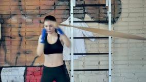 猛击与在健身演播室剧烈力量适合的身体kickboxer的橡皮筋儿的美好的kickboxing的妇女训练 股票视频