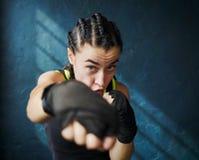 猛击在健身房的画象美好的年轻拳击妇女训练 免版税库存照片