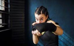 猛击在健身房的画象美好的年轻拳击妇女训练 库存图片