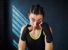 猛击在健身房的画象美好的年轻拳击妇女训练 免版税库存图片