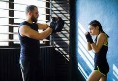 猛击在健身房的画象美好的年轻拳击妇女训练 库存照片
