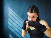 猛击在健身房自由空间, copyspace的画象美好的年轻拳击妇女训练 免版税库存图片