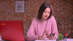 猛击她的在工作场所的愉快的年轻女性智能手机在与近红色膝上型计算机的砖背景前面 股票视频
