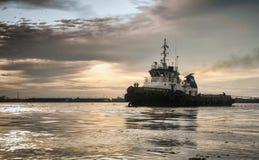 猛拉小船在日落期间的河 免版税库存照片