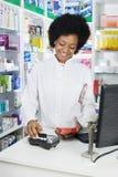 猛击信用卡的女性药剂师,当拿着产品时 免版税库存图片
