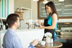 猛击信用卡的女服务员 免版税库存照片
