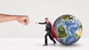 猛击有小地球球形的红色海角和面具的一个小商人一个巨型拳头在他后 图库摄影