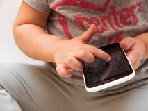 猛击白色智能手机的小孩 库存图片
