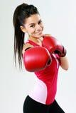 猛击秘密审议与拳击手套的年轻微笑的妇女 免版税库存照片