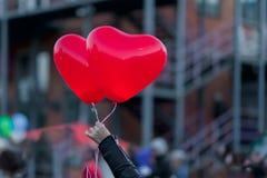 以猩红色灼烧的心脏的形式两个LED气球在晚上在女孩` s手上 对浪漫背景,为 免版税图库摄影