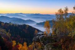 猩红色,红色,桔子,在用在山的云彩盖的黎明天空的天际的黄色条纹 免版税库存照片