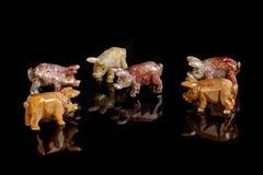 猪小雕象做了石华,碧玉,玻璃,在黑背景的金子 免版税库存图片