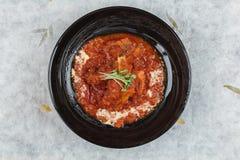 猪排剁牛排顶视图煮沸用西红柿酱和乳酪在washi日文报纸的黑圆的板材服务 免版税图库摄影