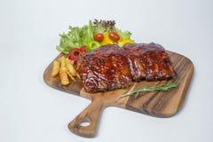 猪排烤肉服务用新鲜的油煎的沙拉和法语 免版税库存照片