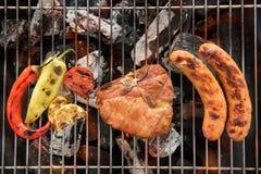 猪排牛排和菜用香肠在一火焰状BBQ gril 库存照片