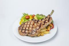 猪排牛排服务用新鲜的油煎的沙拉和法语 免版税图库摄影