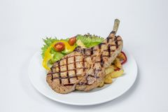 猪排牛排服务用新鲜的油煎的沙拉和法语 库存图片