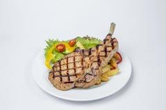 猪排牛排服务用新鲜的油煎的沙拉和法语 图库摄影