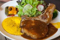 猪排牛排用调味汁和配菜 免版税库存图片