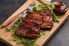 猪排特写镜头在芝麻菜床上的蜂蜜烤了用BBQ调味汁并且变成了焦糖  对啤酒的鲜美快餐在a 免版税库存照片