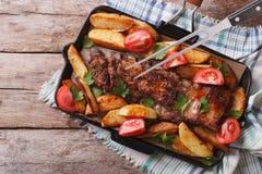 猪排用在平底锅特写镜头的被烘烤的土豆 水平的名列前茅v 库存照片