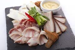 猪油和烟肉在一个黑色的盘子 免版税库存照片