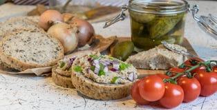 猪肉传播、猪油和酸黄瓜在新鲜的圆的面包,洒与春天和红洋葱 免版税库存照片