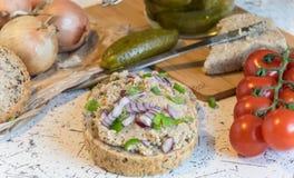 猪肉传播、猪油和酸黄瓜在新鲜的圆的面包,洒与春天和红洋葱 库存图片