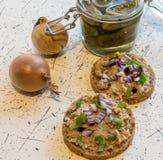 猪肉传播、猪油和酸黄瓜在新鲜的圆的面包,洒与春天和红洋葱 库存照片