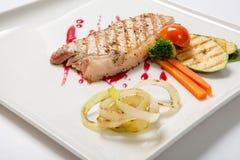 猪肉半生半熟与烤夏南瓜一道配菜调味了酸果蔓酱 免版税库存照片