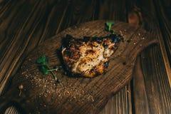 猪肉在委员会木背景的骨头牛排用kenzy的蜂蜜,胡椒 图库摄影
