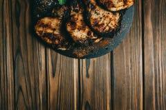猪肉在木背景的骨头牛排用蜂蜜 委员会板岩 见座,胡椒 图库摄影