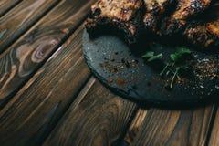 猪肉在木背景的骨头牛排用蜂蜜 委员会板岩 见座,胡椒 免版税图库摄影