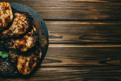 猪肉在木背景的骨头牛排用蜂蜜 委员会板岩 见座,胡椒 库存图片