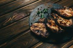 猪肉在木背景的骨头牛排用蜂蜜 委员会板岩 见座,胡椒 免版税库存图片