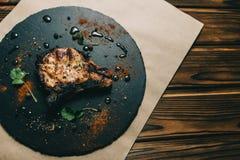 猪肉在木背景的骨头牛排用蜂蜜 委员会板岩 见座,胡椒 库存照片