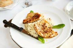 猪肉大奖章用在白色板材、刀子和草本的大麦意大利煨饭 图库摄影