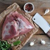 猪肉大火腿和一把大砍的刀子未加工的片断  免版税库存照片