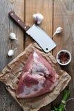 猪肉大火腿和一把大砍的刀子未加工的片断  免版税图库摄影