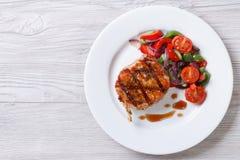 猪肉油煎的片断用菜沙拉,水平的顶视图 库存照片