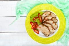 猪肉烘烤了火腿,削减切片用草本,在一块陶瓷板材的胡椒kapi 免版税库存照片