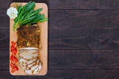 猪肉烘烤了火腿,削减切片用草本,在切板的胡椒kapi在黑暗的木背景 免版税图库摄影