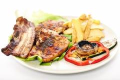 猪肉牛排、土豆和菜 免版税库存图片