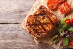 猪肉牛排有菜特写镜头水平的顶视图,土气 免版税库存照片