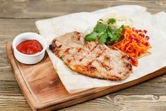 猪肉牛排格栅 服务在一张土气桌上的一个木板 烧烤店菜单,一系列的照片不同 免版税库存照片
