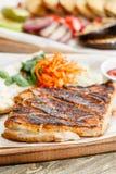 猪肉牛排格栅 服务在一张土气桌上的一个木板 烧烤店菜单,一系列的照片不同 库存图片