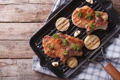 猪肉牛排用在平底锅格栅的葱,水平的顶视图 免版税图库摄影