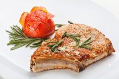 猪肉牛排用在用小树枝装饰的板材的蕃茄上升了 图库摄影